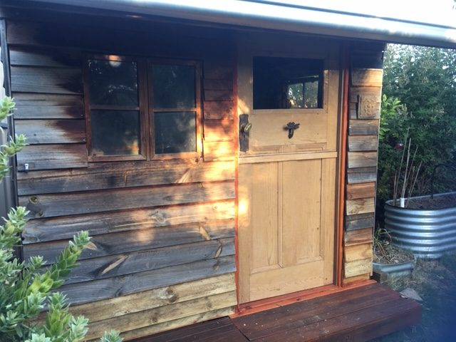The front of the wooden potting shed showing a wooden door with a dragonfly knocker.