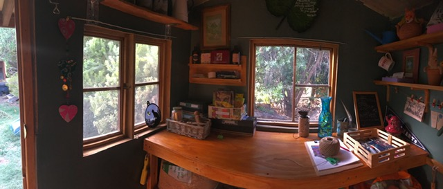 A panoramic photograph of the wooden bench in the shed.