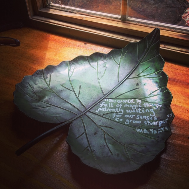 "A leaf-shaped plate with the words of W B Yeats inscribed ""The world is full of magic things patiently waiting for our sense to grow sharper""."