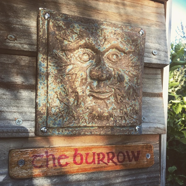 The front of the potting shed showing a stone plaque of a green man and a handmade sign 'The Burrow'